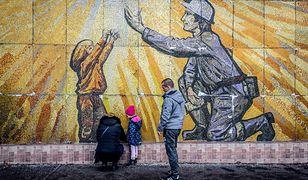 Ludzie kładą kwiaty ku czci ofiar katastrofy w Karvinie przed muralem nieopodal kopalni
