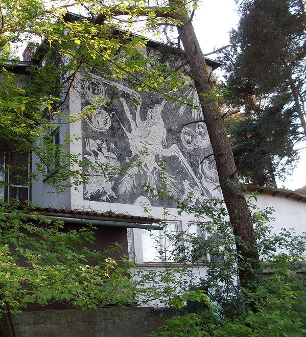 W rzeczywistości dom otaczają modrzewie, które zasłaniają częściowo elewację.