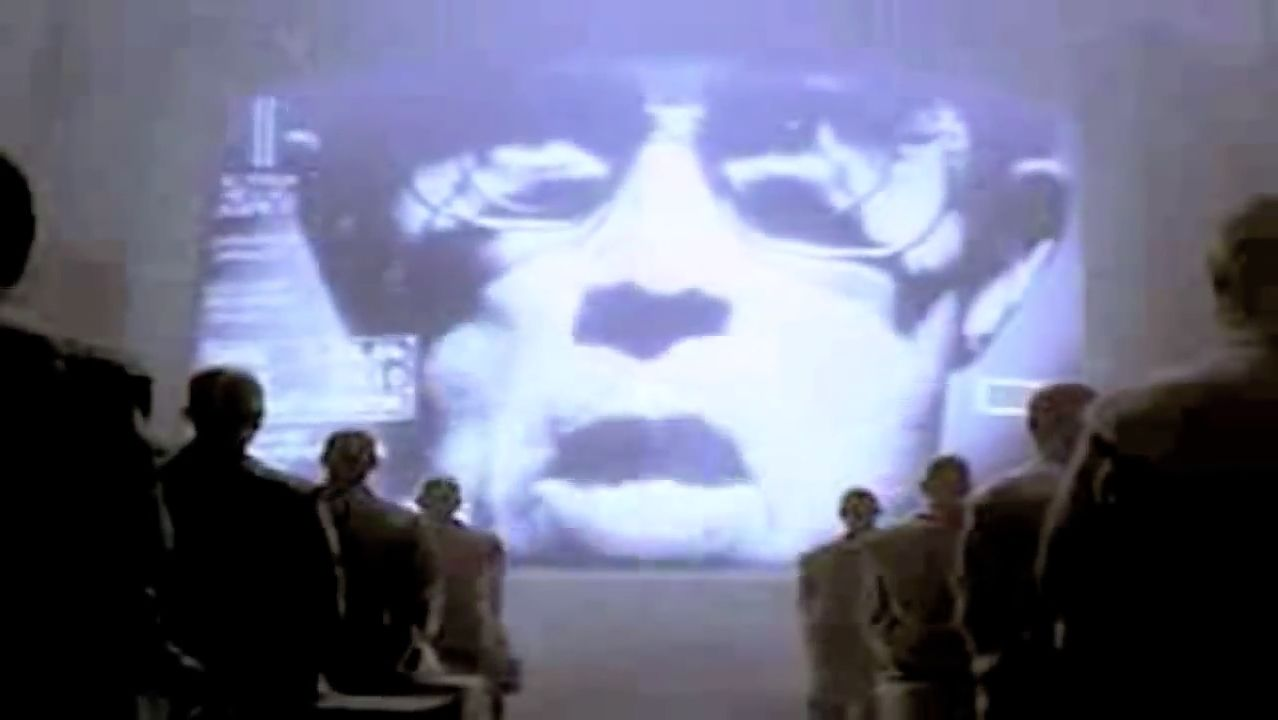 Piekło zamarzło, IBM kupuje komputery Apple - Twarz przemawiająca do tłumu jednolitych, szarych ludzi miała symbolizować Big Blue. ...Stworzyliśmy, po raz pierwszy w całej historii, ogród czystej ideologii, gdzie każdy pracownik może rozkwitać, bezpieczny od organizmów pełnych sprzecznych myśli.