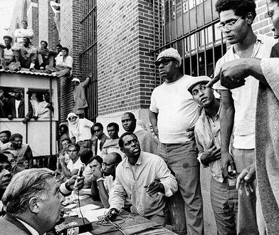 """Komisarz Russell Oswald (siedzi, lewy dolny róg) podczas negocjacji z przywódcami więźniów wśród których są Frank """"Big Black"""" Smith (w okularach przeciwsłonecznych) oraz L.D. Barkley (drugi od prawej). (Dzięki uprzejmości """"New York Timesa"""")"""
