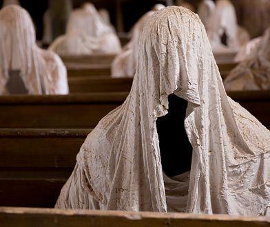 32 postacie w białych szatach zajmują drewniane ławy w kościele we wsi Luková