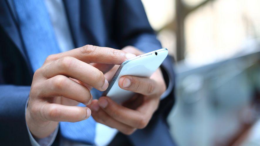 Biznesmen ze smartfonem z depositphotos