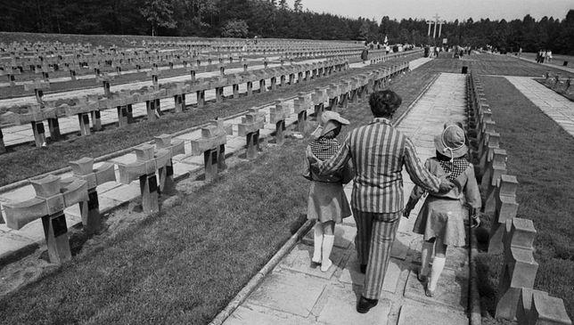 Kobieta ubrana w obozowy pasiak oprowadza dzieci po cmentarzu w Palmirach, 1985 r.