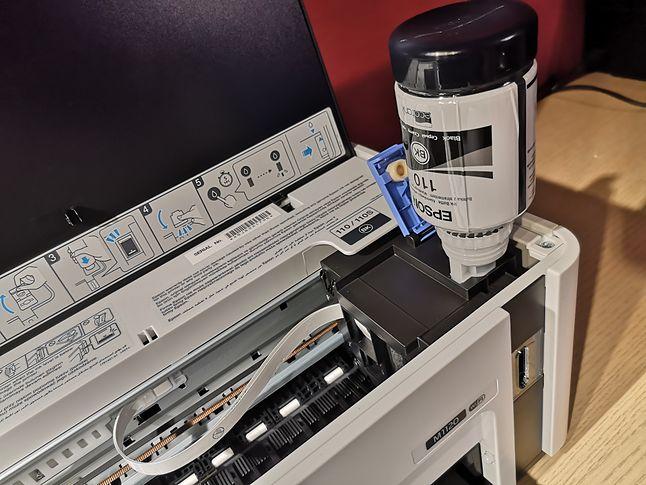 Tusz grawitacyjnie spływa z butelki do pojemnika w drukarce.