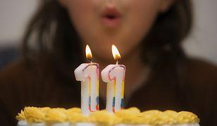 Dziewczynka zdmuchuje świeczki na urodzinowym torcie