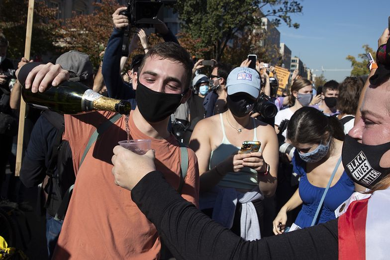 Młodzi Amerykanie świętują z szampanem zwycięstwo Bidena w Waszyngtonie niedaleko Białego Domu
