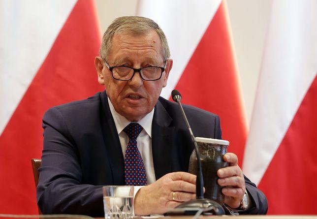 Jan Szyszko trzyma w rękach słoik z kornikami