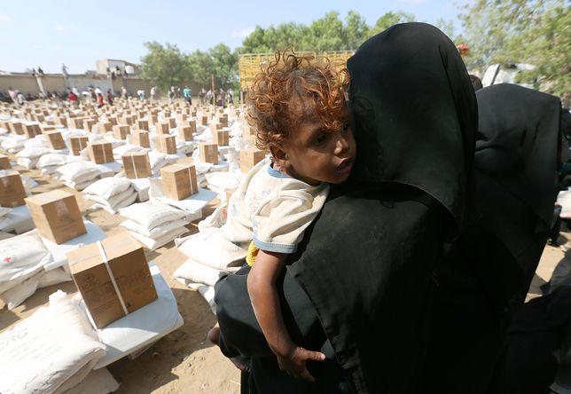 Kobieta z dzieckiem w punkcie wydawania pomocy w Jemenie