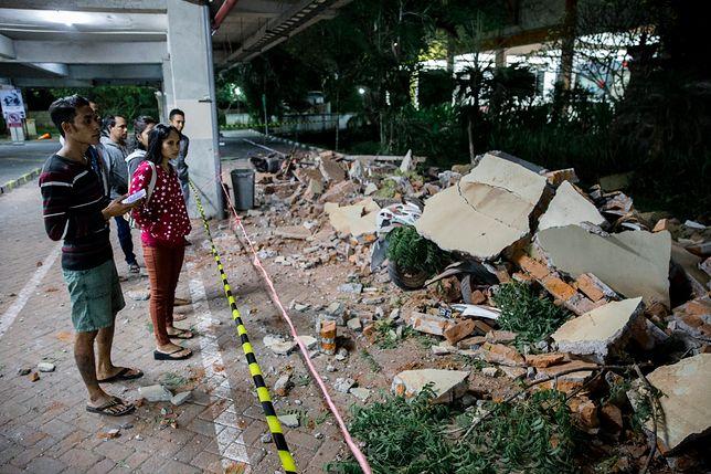 Mieszkańcy Bali patrzą na zniszczone centrum handlowe w wyniku trzęsienia ziemi