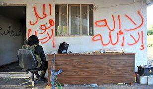 """Syryjski bojownik deklarujący się jako członek grupy """"Szura Taliban Islam"""". Napis po prawej stronie: """"Nie ma boga prócz Allaha"""", po lewej: """"Rozwiązaniem jest Islam"""" - sztandarowe hasło Bractwa Muzułmańskiego"""