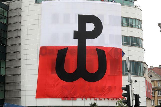 """Warszawa. Godzina """"W"""" na skrzyżowaniu ul. Targowej i al. Solidarności oraz prezentacja flagi ze znakiem Polski Walczącej"""