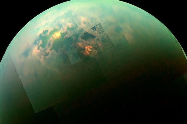 Jasne chmury węglowodorowe nad północnym biegunem Tytana (struktura w kształcie strzałki) oraz odbicie światła od tafli mórz złożonych z ciekłego metanu i etanu (na lewo od strzałki)