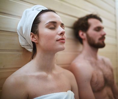Pleased woman enjoying time in sauna with her husband