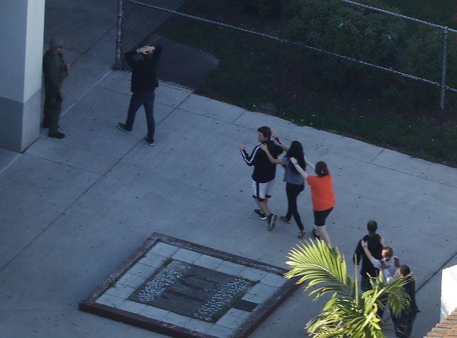 Ludzie wyprowadzani ze szkoły średniej Marjory Stoneman Douglas High School po strzelaninie w Parkland