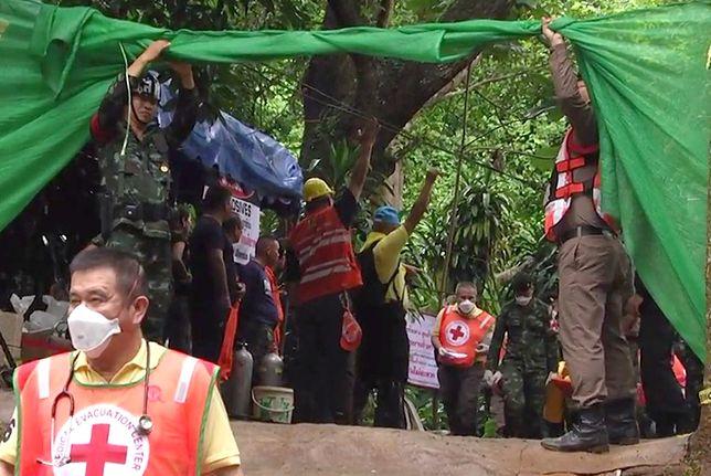 Akcja ratunkowa w Tajlandii: ratownicy niosą jednego z uratowanych chłopców do karetki