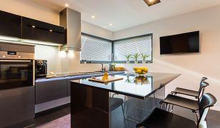 Monolityczna kuchenna zabudowa doskonale czuje się w towarzystwie czarnych i grafitowych blatów.