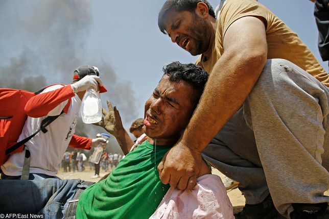Palestyńczycy udzielają pomocy demonstrantowi postrzelonemu przez Izraelczyków