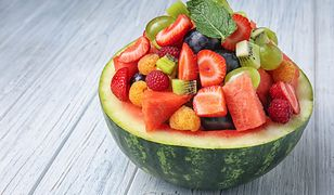 Delicious fruit salad in watermelon bowl on light wooden table