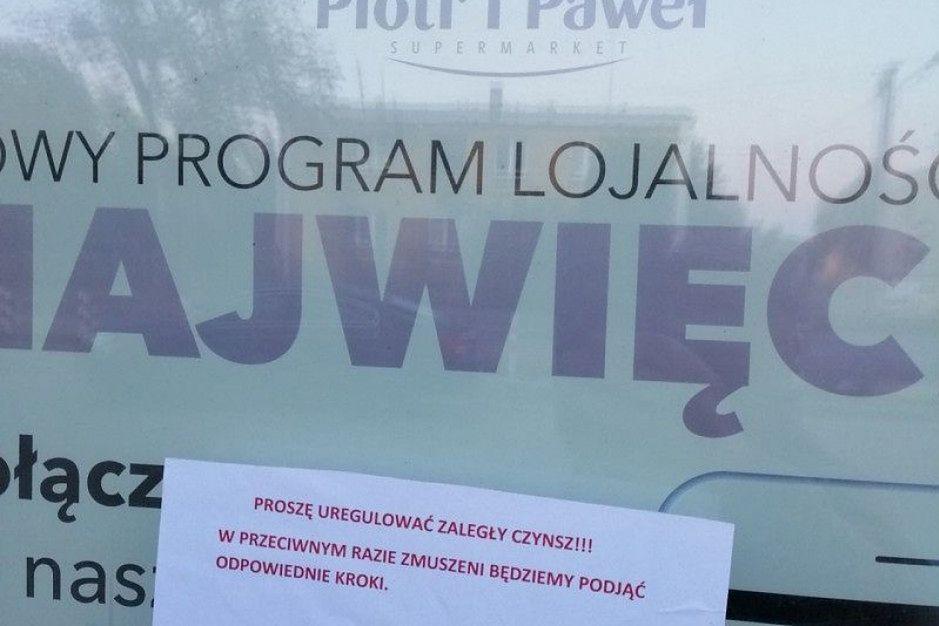 """Sklep Piotr i Paweł. Zastawione wejście i karta z napisem """"zapłać czynsz"""""""