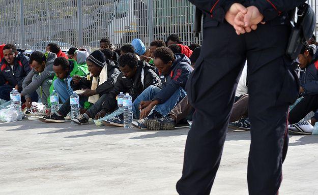 Włoski policjant pilnuje grupy imigrantów; Lampedusa