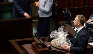 Poseł PO Sławomir Nitras z workiem trocin, który wręczył politykom PiS w Sejmie