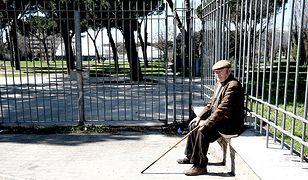 Zdjęcie poglądowe. Starszy mężczyzna siedzi przed jednym z parków w Rzymie.