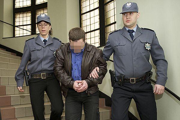Policjanci prowadzą Romana M. do aresztu