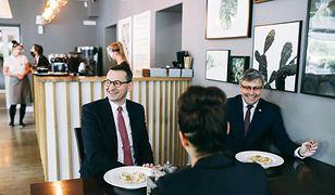 Premier w restauracji, z obcymi osobami przy jednym stoliku.