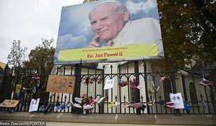 Akcja Baby Shoes Remember przeciwko pedofilii w Kościele. Dziecięce buciki na ogrodzeniu kościoła św. Floriana w Krakowie - pod zdjęciem Jana Pawła II