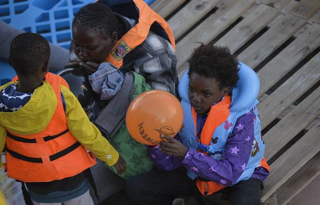 Mali imigranci bawią się balonami po tym, jak zostali uratowani podczas akcji ratunkowej na libijskim wybrzeżu