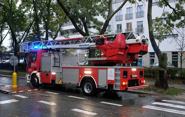 Warszawa. Strażacy pracują w alei Jana Pawła II. Z wieżowca Varso Tower spadają kawałki lodu.