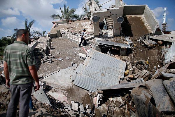 Palestyńczycy przeglądają ruiny swojego domu po izraelskim bombardowaniu