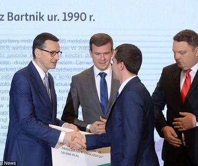 Mateusz Morawiecki przyznaje stypendium Tomaszowi Bartnikowi. Obok minister sportu Witold Bańka i prezes KGHM Marcin Chludzinski