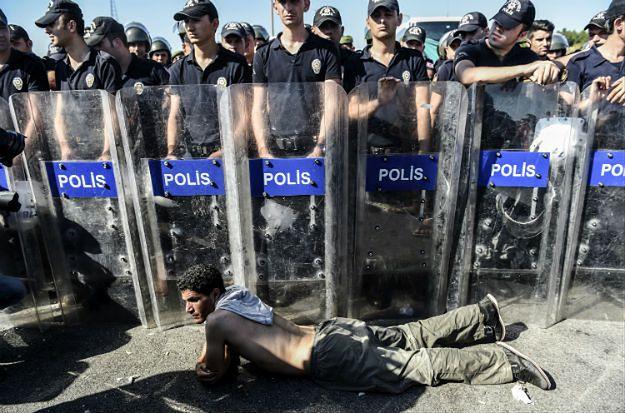 Syryjski uchodźca leży przed szpalerem tureckich policjantów