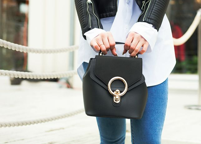 Fashion and Beauty. The girl is holding a fashionable small handbag in hand. Close-up, street-style. Part of the body. Outdoor.