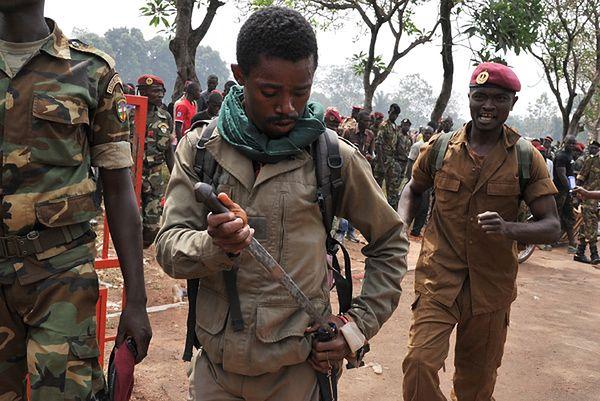 Jeden żołnierzy chowa nóż po tym, jak wziął udział w linczu