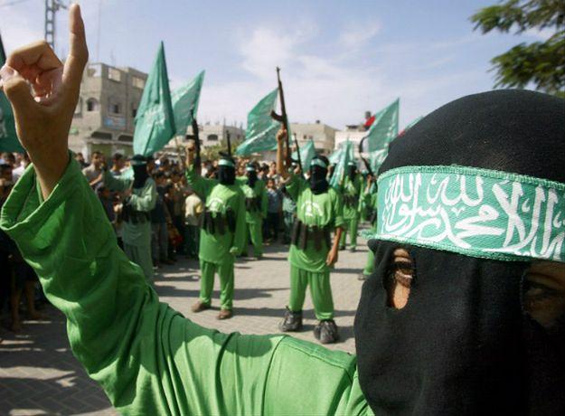 Brygady Izz ad-Dina al-Kassama, zbrojne skrzydło Hamasu. W tle bojownicy z pasami szahida