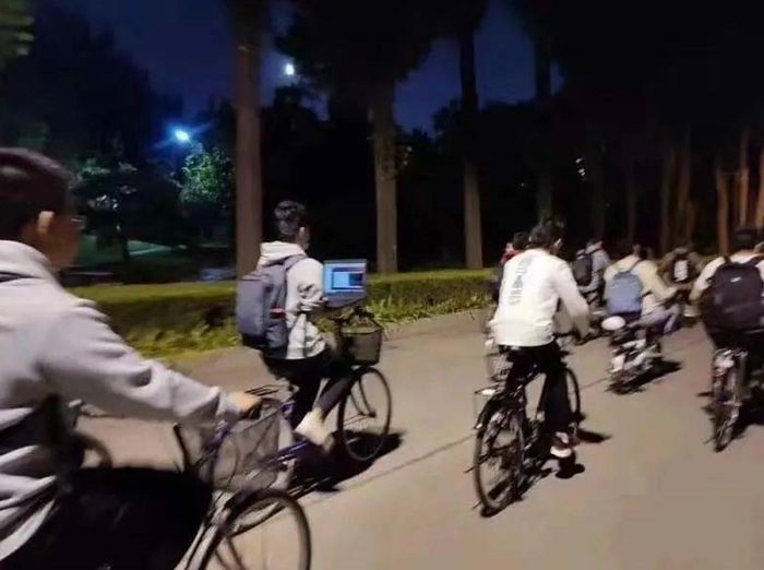 Chiny: Student jedzie na rowerze i jednocześnie pracuje na laptopie