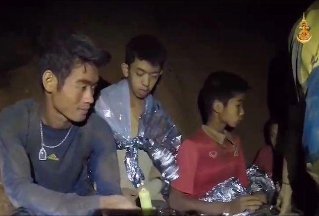 Odnalezione, ale jeszcze nie uratowane, dzieci i ich trener (na pierwszym planie) koczują na małej półce skalnej