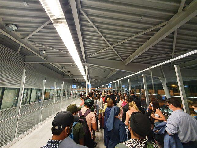 Setki osób w korytarzu na lotnisku w Warszawie. Kilkadziesiąt minut oczekiwania