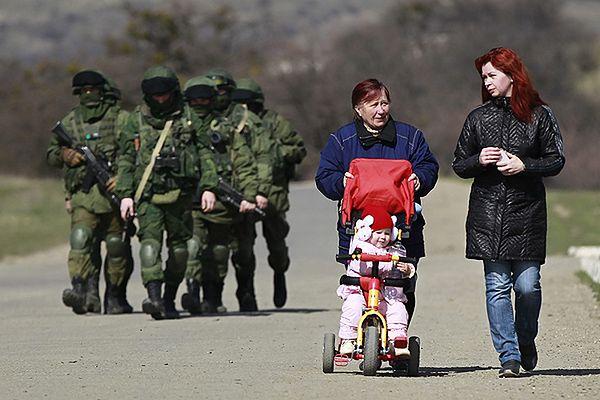 Mieszkanki Krymu na spacerze. W tle maszerujący żołnierze
