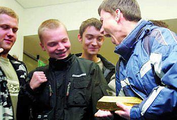 Uczniowie Liceum nr 9 w Katowicach, zwiedzający gmach NBP, dźwigają sztabę złota o wadze 12,5 kg