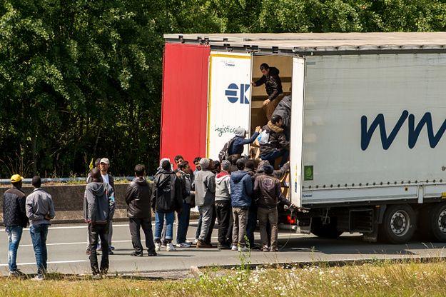 Imigranci wskakują do ciężarówki stojącej na drodze prowadzącej do Eurotunelu