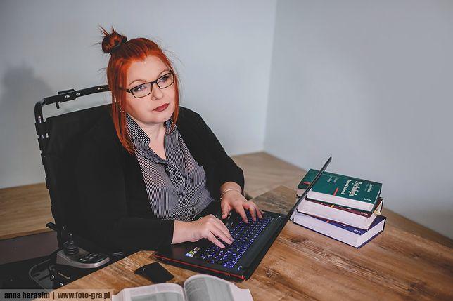 kobieta siedzi na wózku przed biurkiem i patrzy w dal