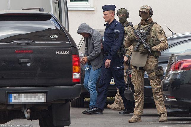 Marek Falenta w otoczeniu uzbrojonej eskorty.