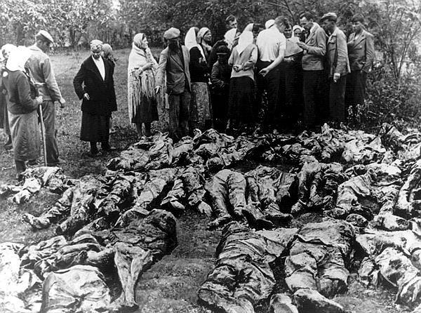 Ludzie z okolicznych wsi stoją nad jednym z odkrytych masowych grobów w Katyniu