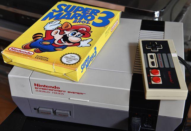 """Konsola Nintendo z lat 80-tych wraz z grą """"Super Mario Bros. 3"""""""