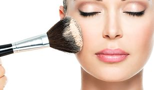 Closeup portrait of a woman  applying dry cosmetic tonal foundation  on the face using makeup brush.