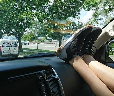 Pasażer trzymający nogi na desce rozdzielczej