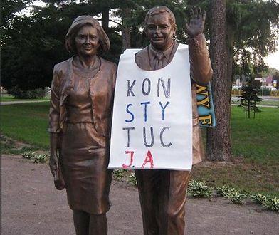 """67-latek, który przyozdobił pomnik Lecha i Marii Kaczyńskich banerem z napisem """"Konstytucja"""" usłyszał zarzut znieważenia pomnika. (Twitter)"""